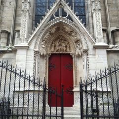 Stone carving and ironwork round a side door at Notre Dame cathedral