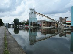 A mirror image lends grandeur to the cement works on Canal St Denis