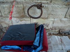 A neat pile of bedding by a worn ring - a bridge offers shelter to those with no other moorings