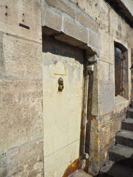 Halfway up a flight of steps, hidden behind a parapet, a rusty iron door with a lion's head knocker