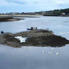 Figures who might have walked straight out of a Lowry painting prepare salmon nets on a sandbank in the River Tweed