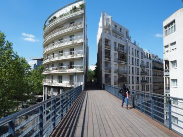 The Promenade Plantée crosses a road on an old railway bridge and dives through the layers of a housing block - there's a layer of shops and offices below the bridge