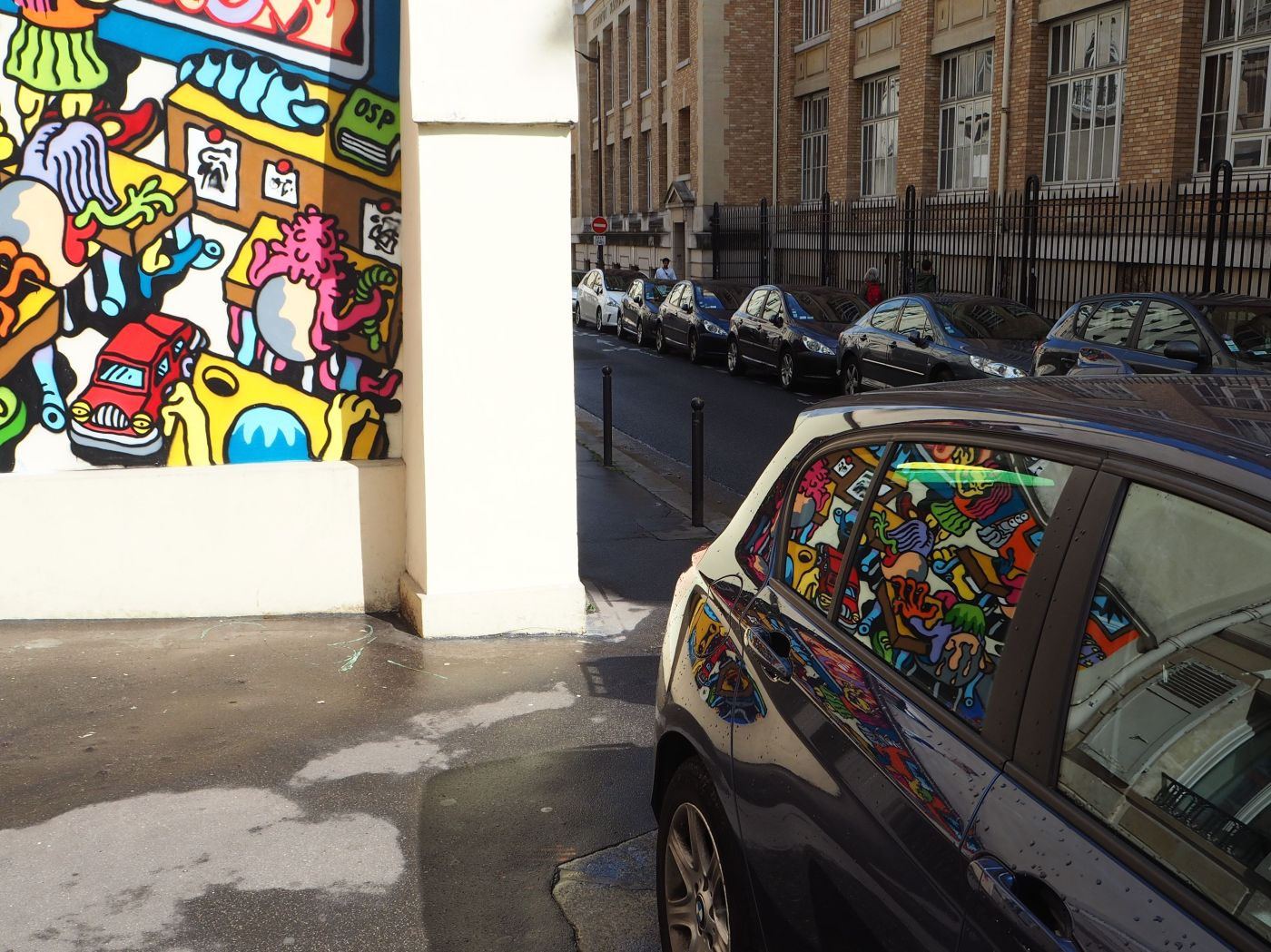 mural by omick reflected in car window paris