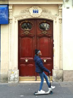ornate door and passing girl on scooter paris