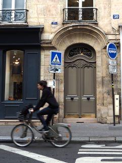 taupe door and passing velib rider paris 6