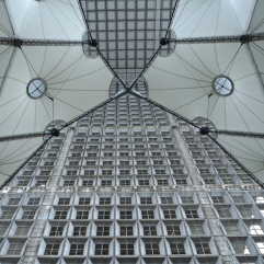 The taught lines of a canopy cross the grid of windows in the Grande Arche at La Défense
