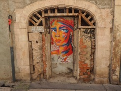 This portrait in this ancient doorway and the one in the headline image are the work of local artist Manyoly
