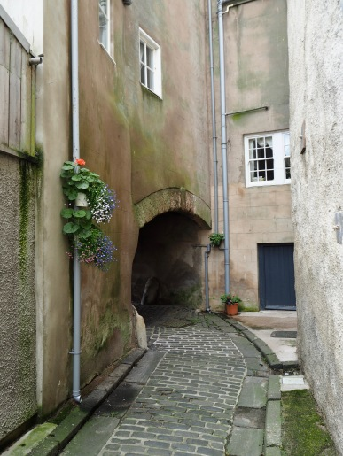 Dewar's Lane curves round out of sight under an archway