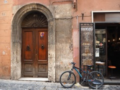 and a mountain bike contrasting with an ancient door in Rome