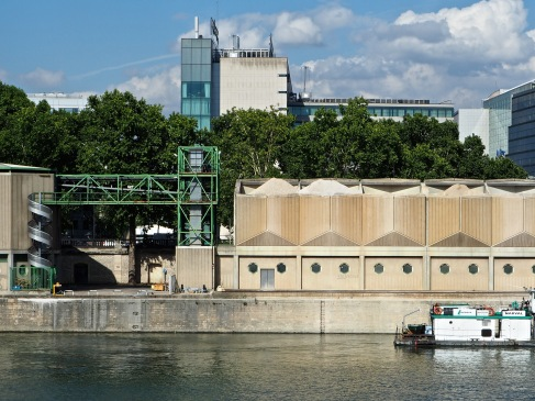 Trees and buildings line the street above a quayside cement works while a barge waits on the river below