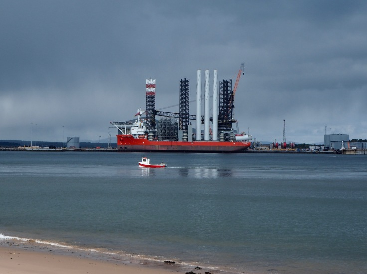 contrast in scale - small fishing boat passes the Pacific Orca wind farm installation vessel