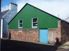 A bright blue door on a green painted workshop that may be older than it looks