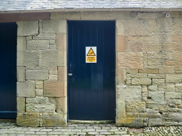 The warning reads 'Unprotected edge' - imagination supplies the pit beyond the store room door