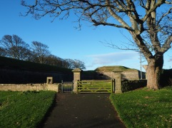Keep following the path round the ramparts and you'll come to a gate...