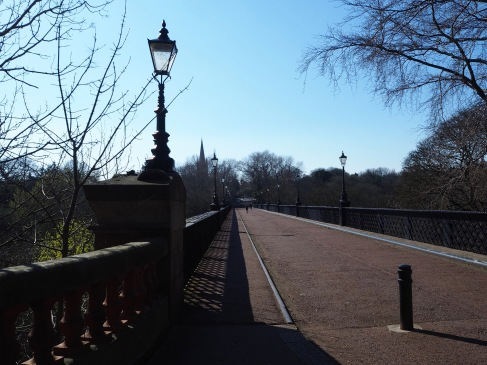 Shadows, lamp posts and a distant spire on Newcastle's Armstrong Bridge