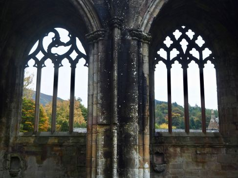 The stone tracery of these windows, at Melrose Abbey, divides the landscape view beyond into a pattern of geometric shapes.